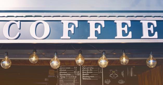 De voorzijde van de koffiewinkel met bollichten en bord