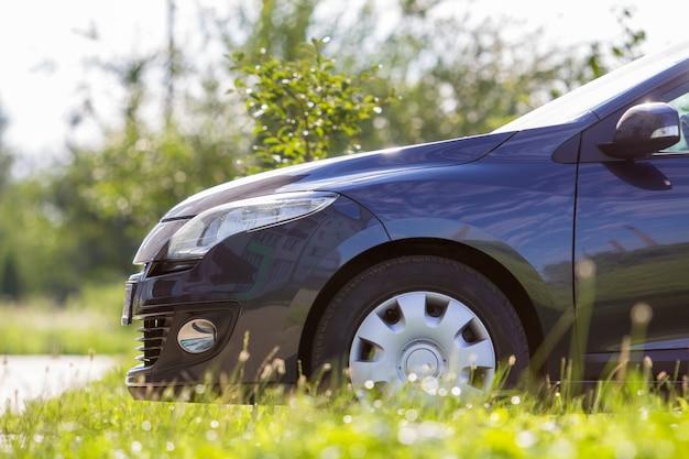 De voorzijde van het close-updetail van moderne nieuwe glanzende lege zwarte auto geparkeerde buitenweg in hoog gras op heldere de zomer zonnige dag
