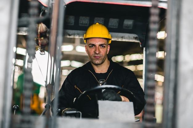 De vorkheftruckchauffeur van de kaukasische fabrieksarbeider in lading logistieke zeevaartindustrie.