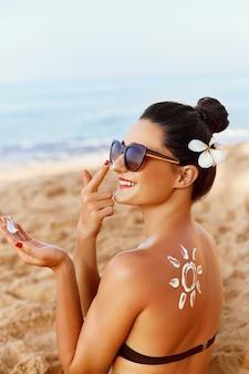 De vorm van de zon is gemaakt van zonnebrandcrème op de rug van een jonge vrouw