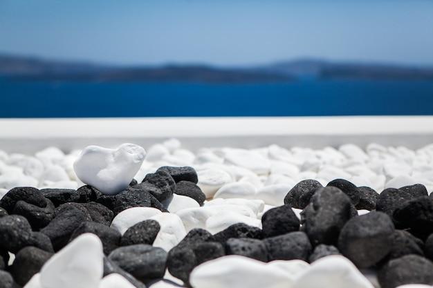 De vorm van het witte steenhart op een achtergrond van blauwe overzees en hemel