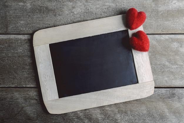 De vorm van liefdeharten en leeg schoolbord op houten achtergrond