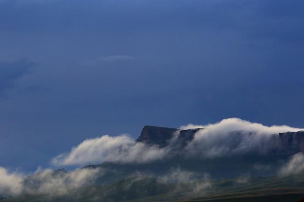 De vorming van mist en wolken tijdens zonsondergang over de bergen. gefotografeerd in de kaukasus, rusland.