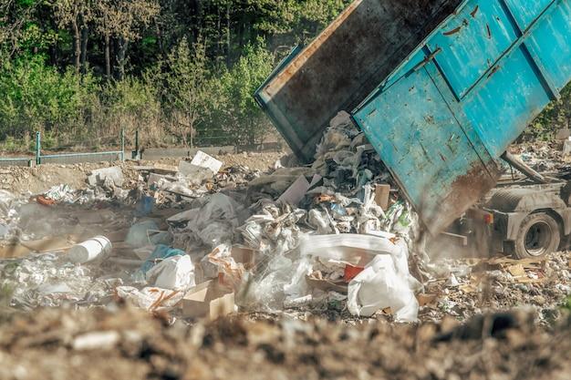De vrachtwagen dumpt gemengd afval op de stortplaats. afvalopslag, ecologische oplossingen