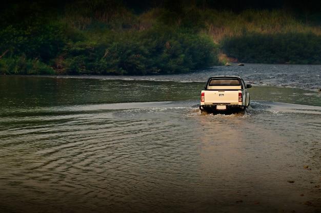 De vrachtwagen op de rivier in het bos