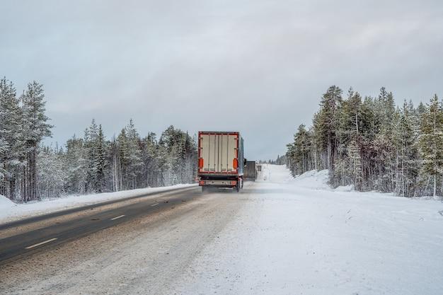 De vrachtwagen rijdt over een besneeuwde poolweg.