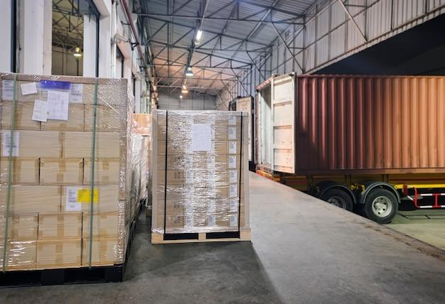 De vrachtwagen van de ladingsaanhangwagen geparkeerd laden bij dokmagazijn