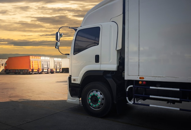De vrachtwagen van de ladingscontainer die bij avondrood wordt geparkeerd