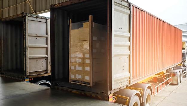 De vrachtwagencontainer laadt vrachtlading in het magazijn