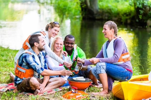De vrienden barbecueën na sporten in bos het drinken bier
