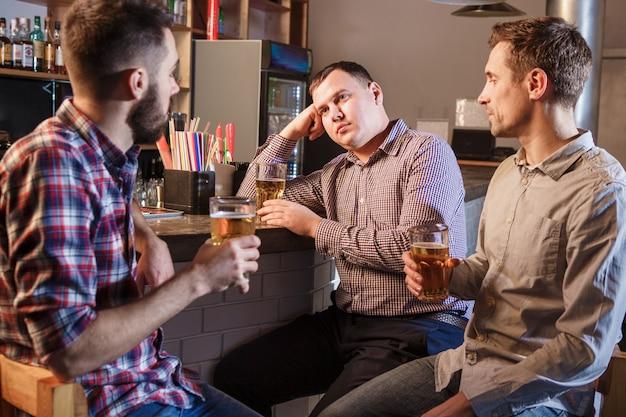 De vrienden drinken bier aan balie in pub