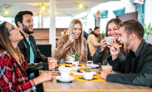 De vrienden groeperen het drinken cappuccino bij koffiebar