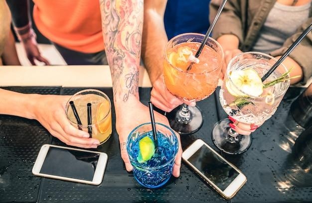 De vrienden groeperen het drinken cocktail bij het restaurant van de manierbar