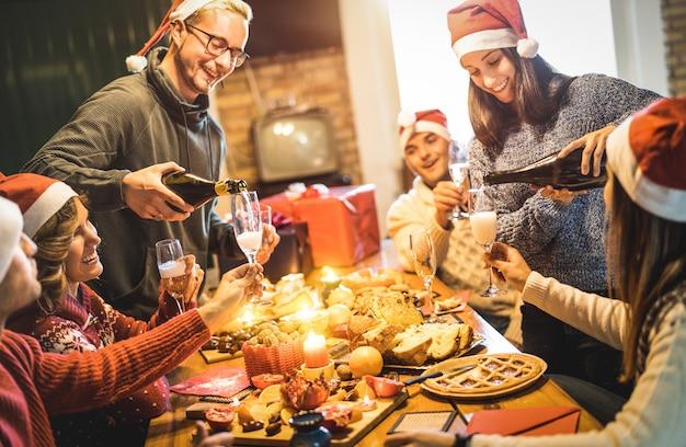 De vrienden groeperen zich met santahoeden die kerstmis met champagne en snoepjesvoedsel thuis diner vieren