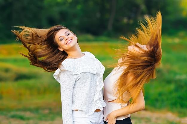 De vrienden staan een voor een en zwaaien met hun haar tegen de achtergrond van gras en bomen