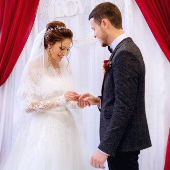 De vriendin van de bruid kijkt toe terwijl de bruid een trouwring draagt