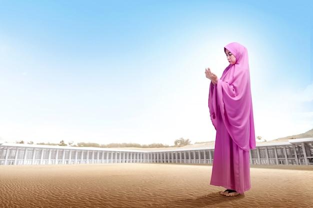 De vrij aziatische vrouw in roze sluier die zich op woestijn bevinden heft de handen op en kijkt neer