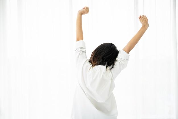 De vrij aziatische vrouw in wit overhemd maakt het uitrekken zich na wakker van het bed in ochtend, vrije tijd en comfortabel het levensconcept.