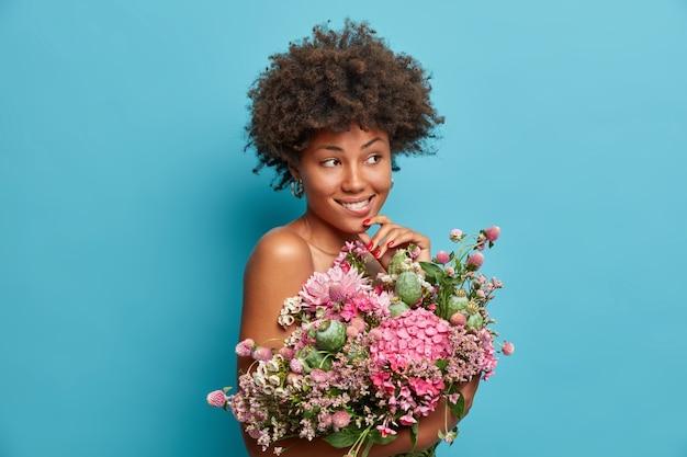 De vrij bedachtzame jonge afro-amerikaanse vrouw staat naakt binnen en houdt een groot boeket bloemen vast, kijkt peinzend en bijt op haar lippen