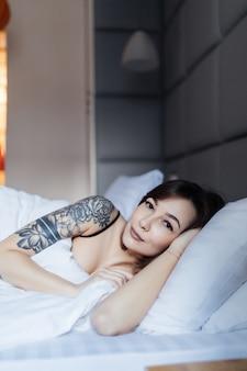 De vrij donkerbruine vrouw met tatoegering legt in het bed op het hoofdkussen in de ochtend in manier modern appartement