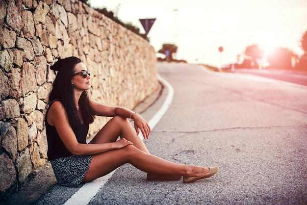 De vrij donkerbruine zitting van het toeristenmeisje op de weg