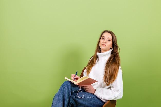 De vrij europese vrouw in toevallige witte geïsoleerde sweater, leuke gelukkige zit op stoel met blocnote en pen