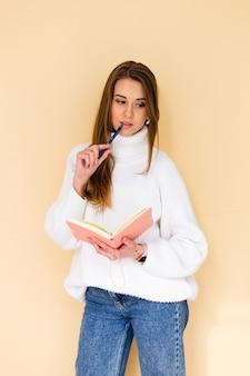 De vrij europese vrouw in toevallige witte sweater isoleerde leuke positief denkende holdingskladblok en pen