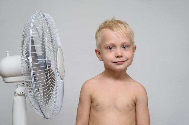 De vrij glimlachende blonde jongen met naakt torso bevindt zich dichtbij een ventilator. zomer concept