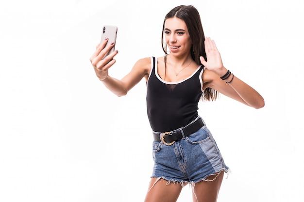 De vrij glimlachende donkerbruine vrouw in zwart overhemd maakt selfie op haar telefoon geïsoleerd