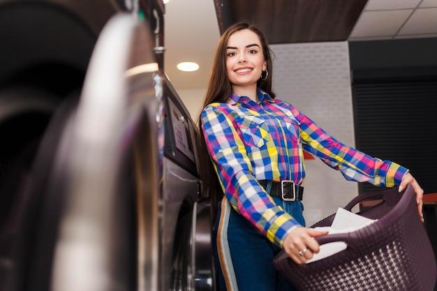 De vrij glimlachende vrouw bij de wasserette houdt een mand van kleren.