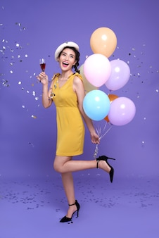 De vrij jonge aziatische vrouw die bij vieringspartij kleurrijke ballon en wijnglas houdt met geniet met confettien die overal op haar vallen. gelukkig nieuwjaar of verjaardagsavond vieren concept