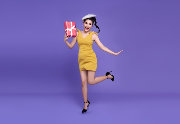 De vrij jonge aziatische vrouw die rood houdt stelt met vreugdevol springen voor. gelukkig nieuwjaar of verjaardagsavond vieren concept. op heldere paarse muur.