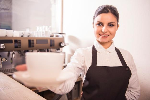 De vrij jonge barista biedt kop van koffie in een koffie aan.
