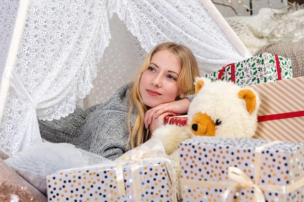 De vrij jonge blonde vrouw die kerstmis giftboxes oplegt, draagt een witte gebreide trui