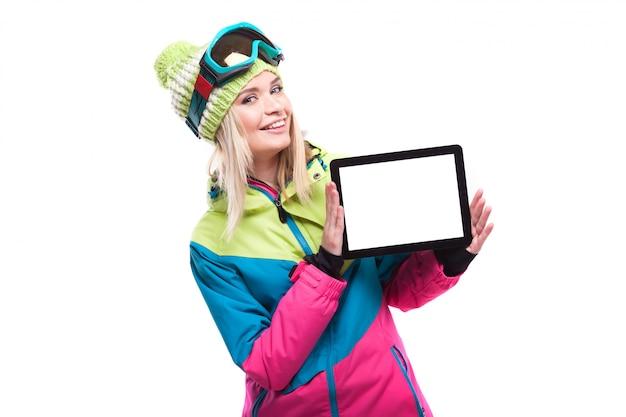 De vrij jonge blondevrouw in kleurrijke sneeuwuitrusting toont lege tablet