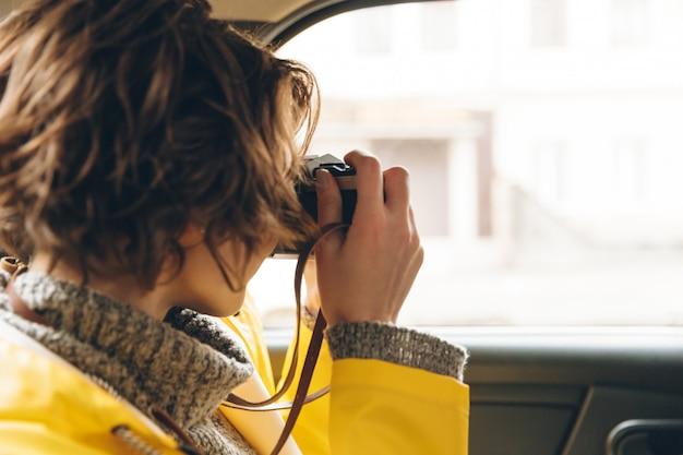 De vrij jonge damefotograaf kleedde zich in regenjas