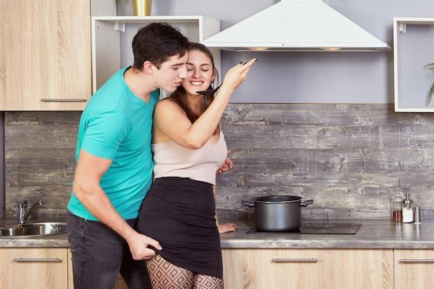 De vrij jonge kaukasische vrouw bereidt maaltijd in keuken voor en voedt haar vriend door stuk voedsel dat bij hem glimlacht.