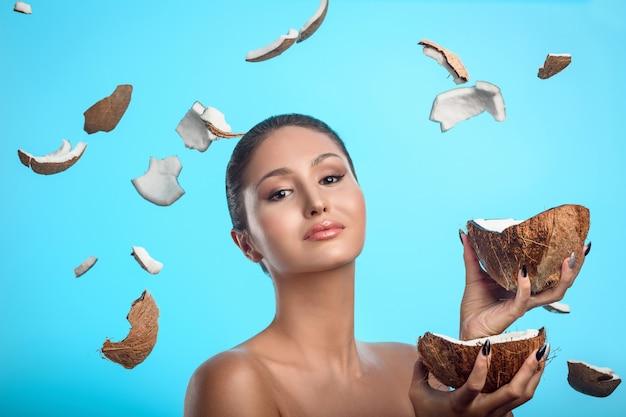 De vrij jonge kokosnoot van de vrouwenholding in haar handen