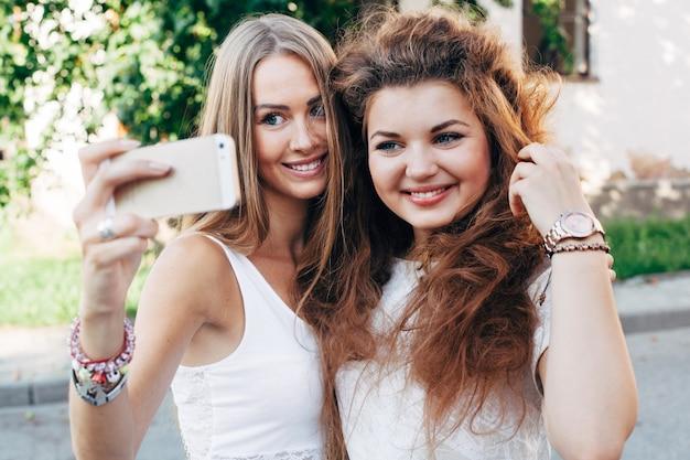 De vrij jonge meisjes die selfie openlucht op de straat in de zomermeisjes doen hebben pret met smartphone die selfie doen