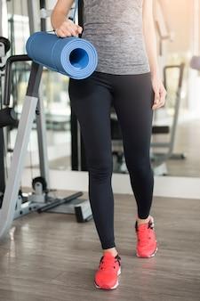 De vrij jonge sportvrouw is training met mat in gymnastiek, gezonde levensstijl