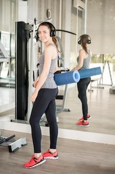De vrij jonge sportvrouw is training met mat in gymnastiek