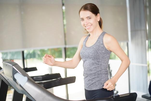 De vrij jonge sportvrouw loopt op tredmolen in gymnastiek