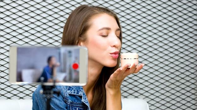 De vrij jonge vrouw blogger presenteert schoonheidsschoonheidsmiddel en zendt livevideo naar sociaal netwerk met smartphonetechnologie uit