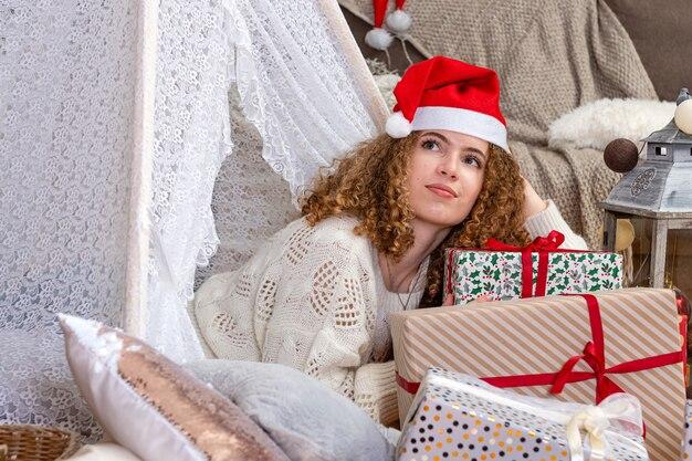 De vrij jonge vrouw die kerstmisgiftboxes oplegt, draagt een gebreide trui en een kerstmuts
