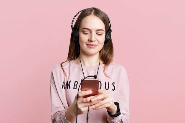 De vrij jonge vrouw geniet van aardige muziek in hoofdtelefoons, bekijkt grappige video's, typt berichten op celtelefoon, terloops gekleed, geïsoleerd over roze muur. mensen, technologie, lifestyle concept