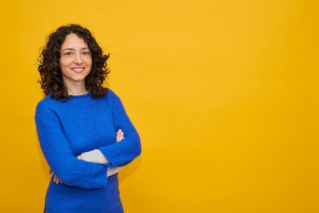 De vrij jonge vrouw glimlacht zelfverzekerd over gele geïsoleerde achtergrond, die blauwe sweater draagt