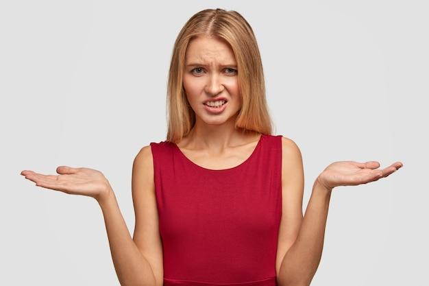 De vrij jonge vrouw haalt schouders op en heeft een ontevreden uitdrukking