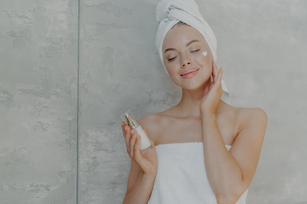 De vrij jonge vrouw houdt fles bodylotion, past gezichtscrème op teint toe