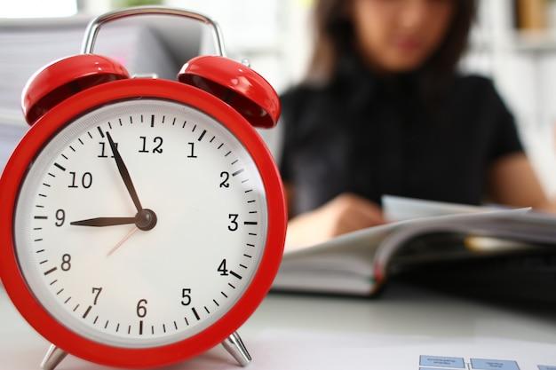 De vrij jonge vrouw in bureau zit aan lijst vroege ochtend