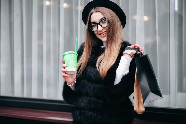 De vrij jonge vrouw in glazen loopt rond de stad met een kop van koffie in haar handen na het lange winkelen